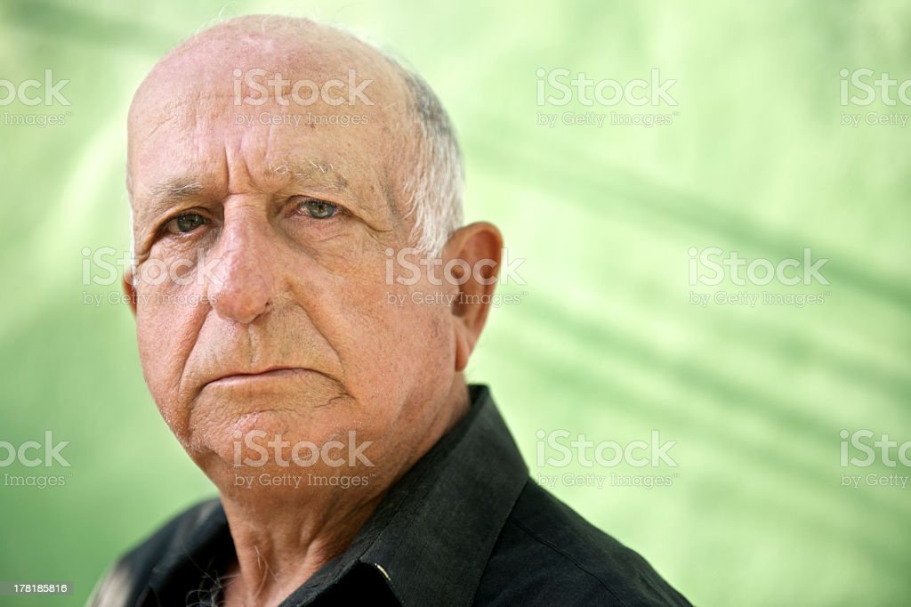 Close-up of older man with serious expression on green stock photo