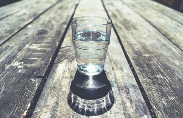 close-up de um vidro da água desobstruída na tabela de madeira - meio cheio - fotografias e filmes do acervo