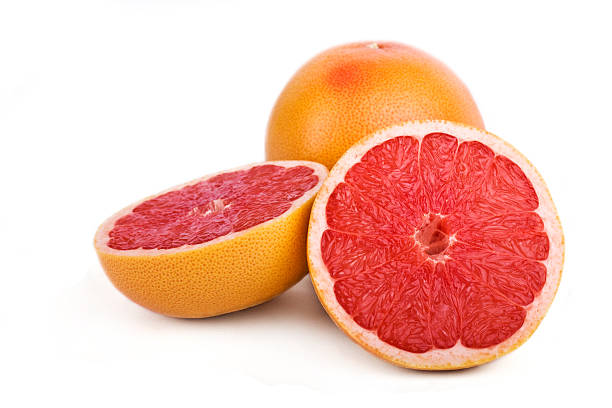 Close-up of one sliced and one full grapefruit stock photo
