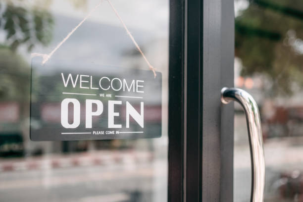 Closeup of open and welcome to store sign board at the door. stock photo
