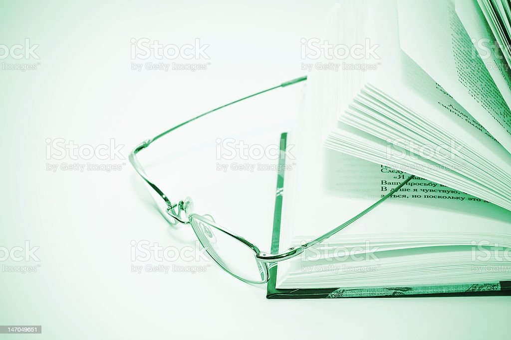 closeup of opened book and glasses royalty-free stock photo