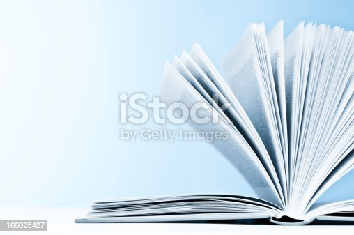 istock Close-up of opened book with pages on light blue background 166025427