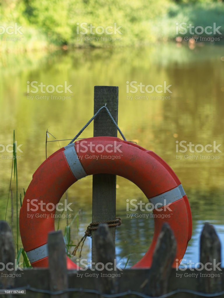 Close-up of orange life buoy, a pond in the background. stock photo
