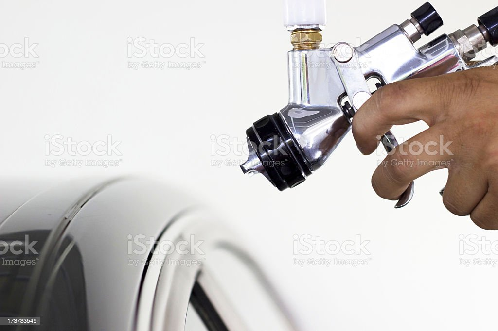 Close-up of paint gun about to be used on car roof stock photo