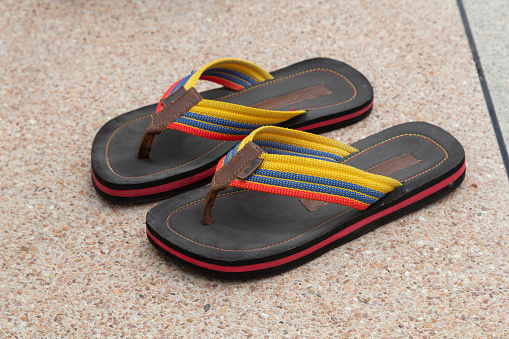 closeup of pair of fabric and rubber sandals with various colors, on the floor, casual style