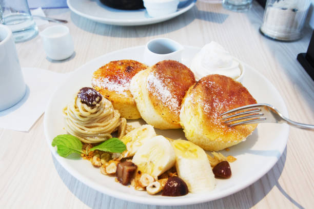 nahaufnahme von pfannkuchen mit früchten in platte - kastanienhonig stock-fotos und bilder