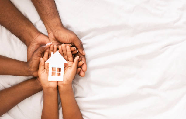 Closeup of paper house in hands of african american family Adoption and family housing concept. Cutout paper house in hands of african american family over white bed sheet background. Closeup, panorama home ownership stock pictures, royalty-free photos & images