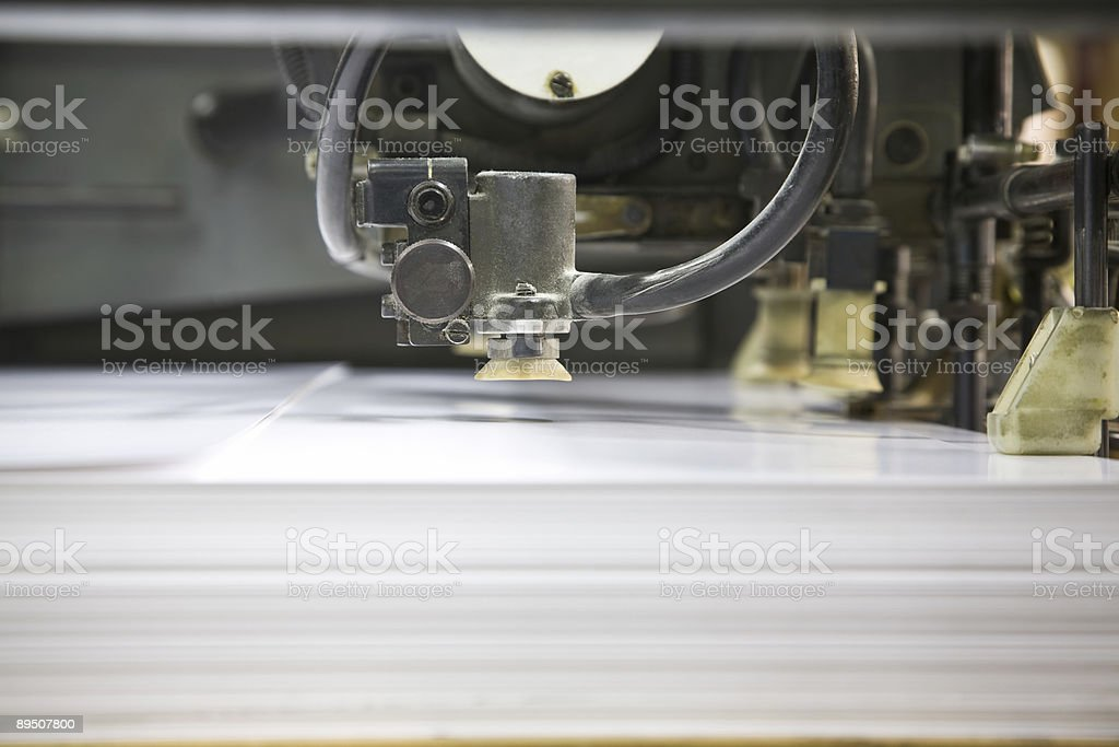 Closeup of Paper Sheets Being Fed Into Printing Press royalty-free stock photo