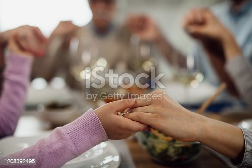 Close-up of extended family holding hands and saying grace before the lunch at dining table.