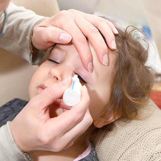 Closeup of parent pouring eye drops in eye her daughter stock photo