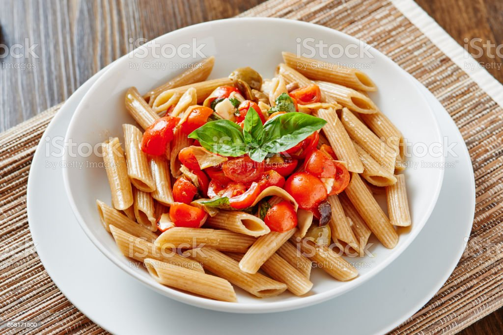 Close-up of pasta penne with cherry tomatoes on white plate surrounded by ingredients - vegan food stock photo