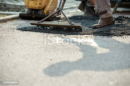 Closeup of patching a bump in the road with new asphalt using rakes to spread the cement mixture.