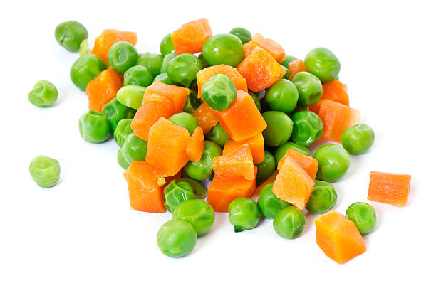 A close-up of peas and carrots stock photo
