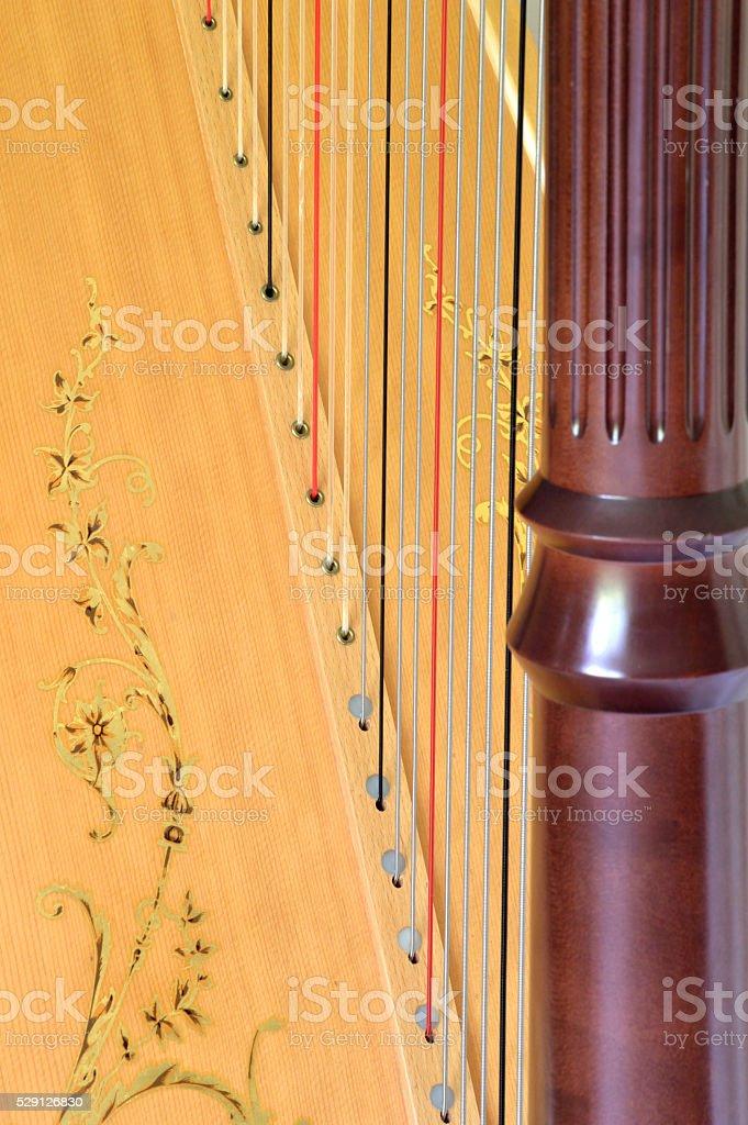 Closeup of pedal harp column strings and soundboard stock photo