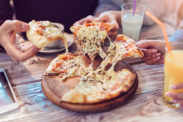 Close-up Of People Hands Taking Slices Of Pizza stock photo