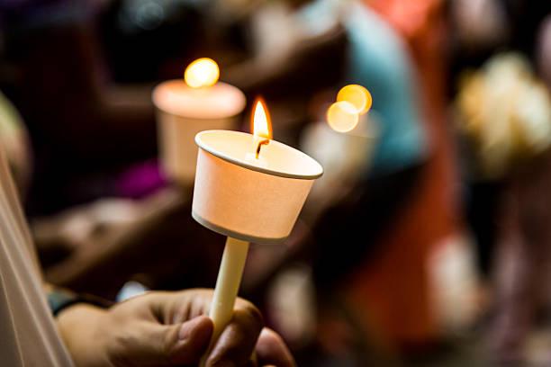 menschen halten nahaufnahme einer kerze mahnwache in dunklen, die hoffnung - osterfeuer stock-fotos und bilder