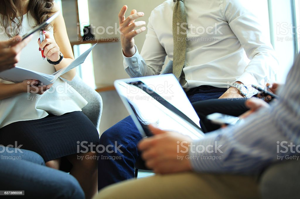Close-up of people sitting on conference together and making notes. stock photo