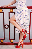 Perfect smooth women's legs in stylish high heels shoes posing with handrail on bridge. Fashionable gorgeous girl in polka dot dress stand on bridge. Girl in urban outfit walks in city. Noise effect