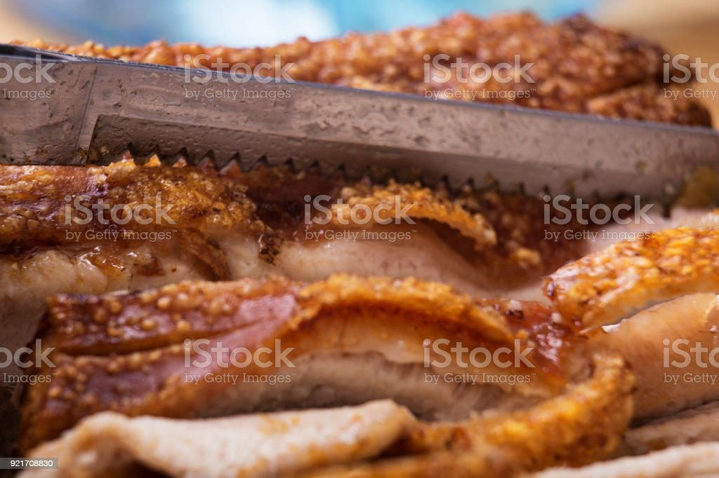 Close-up of perforated knife blade with roasted meat stock photo