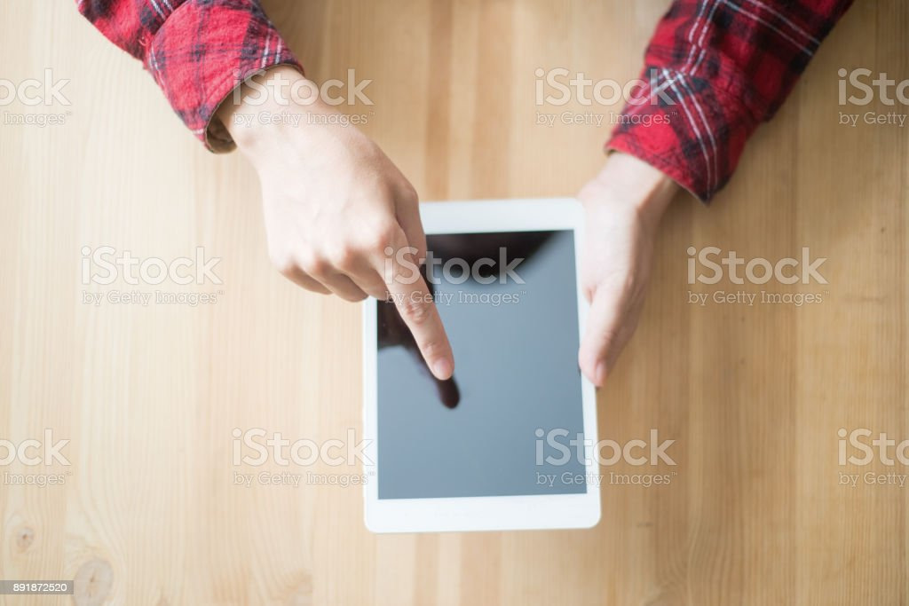 Closeup of Person Browsing on Touchpad at Table stock photo