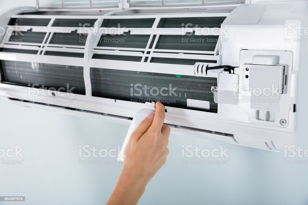 Close-up Of Person Cleaning Air Conditioner stock photo