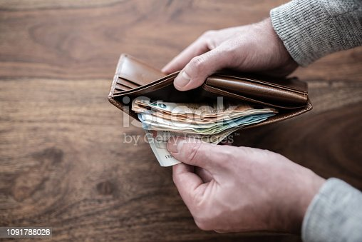istock close-up of person counting stack of paper cash in wallet 1091788026