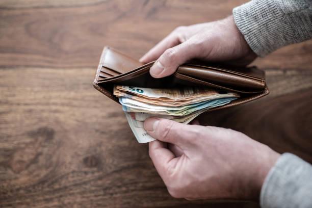 nahaufnahme einer person zählen stapel papier geld im portemonnaie - eurozahlen stock-fotos und bilder