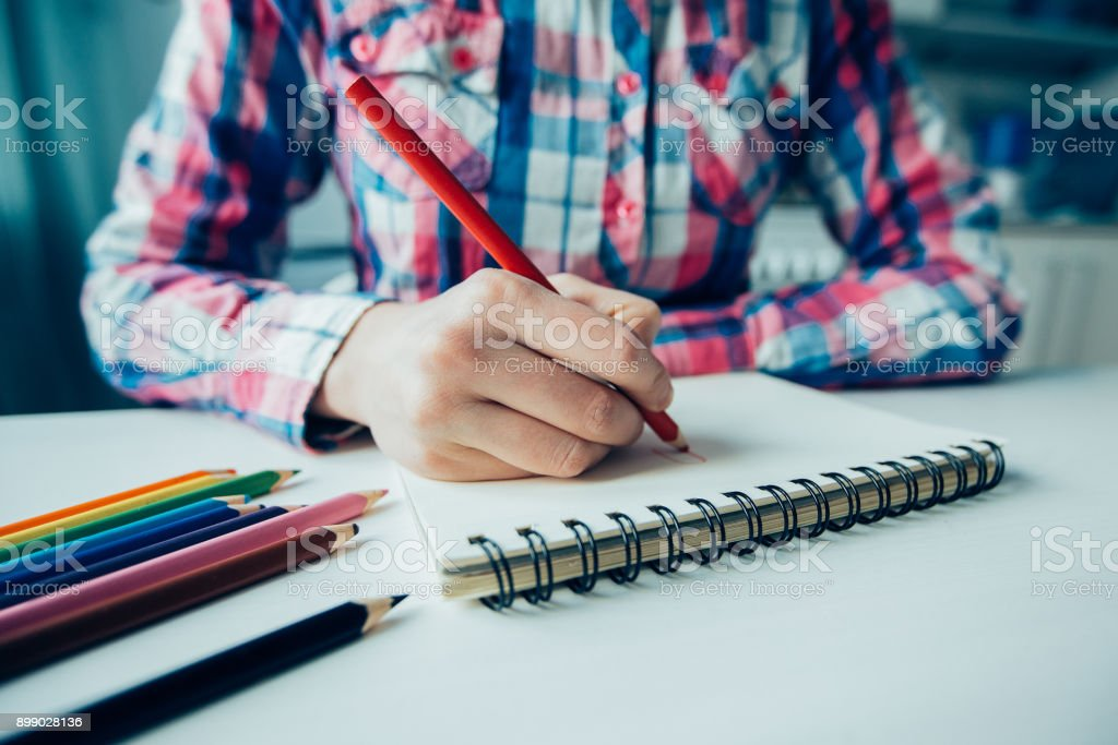 Closeup of Person Drawing With Colored Pencils stock photo