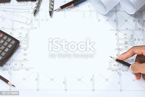 istock Close-up of person engineer hand drawing plan on blue print with architect instrument at office desk. 821379930