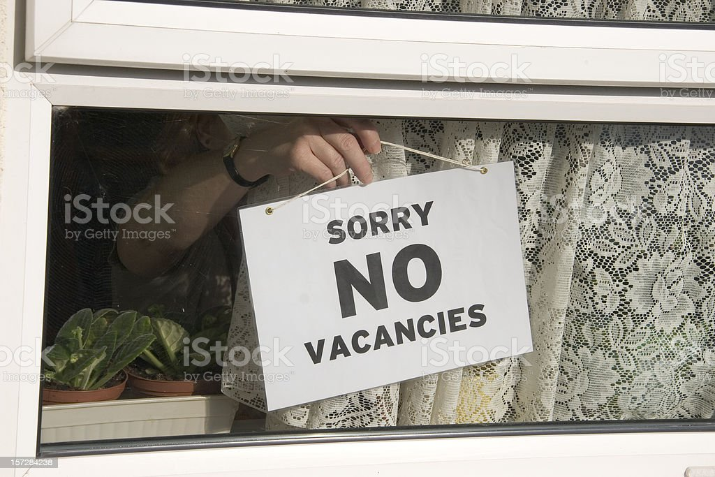Close-up of person hanging No Vacancies sign on window stock photo