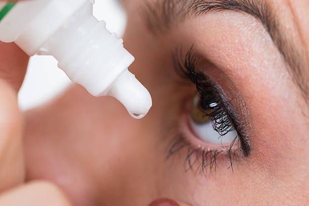 Close-up Of Person Pouring Drops In Eyes stock photo