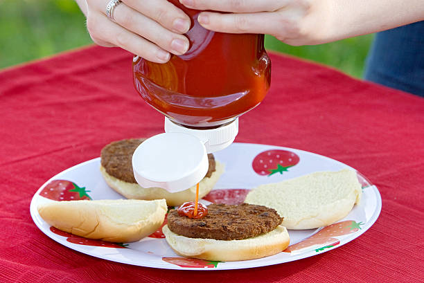 close-up of person putting ketchup on hamburger - ketchup bottle stock photos and pictures