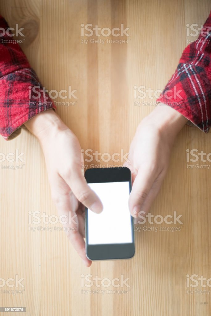 Closeup of Person  Sitting at Table with Smartphone stock photo