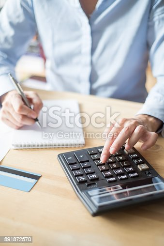 645670208istockphoto Closeup of Person Writing and Using Calculator 891872570