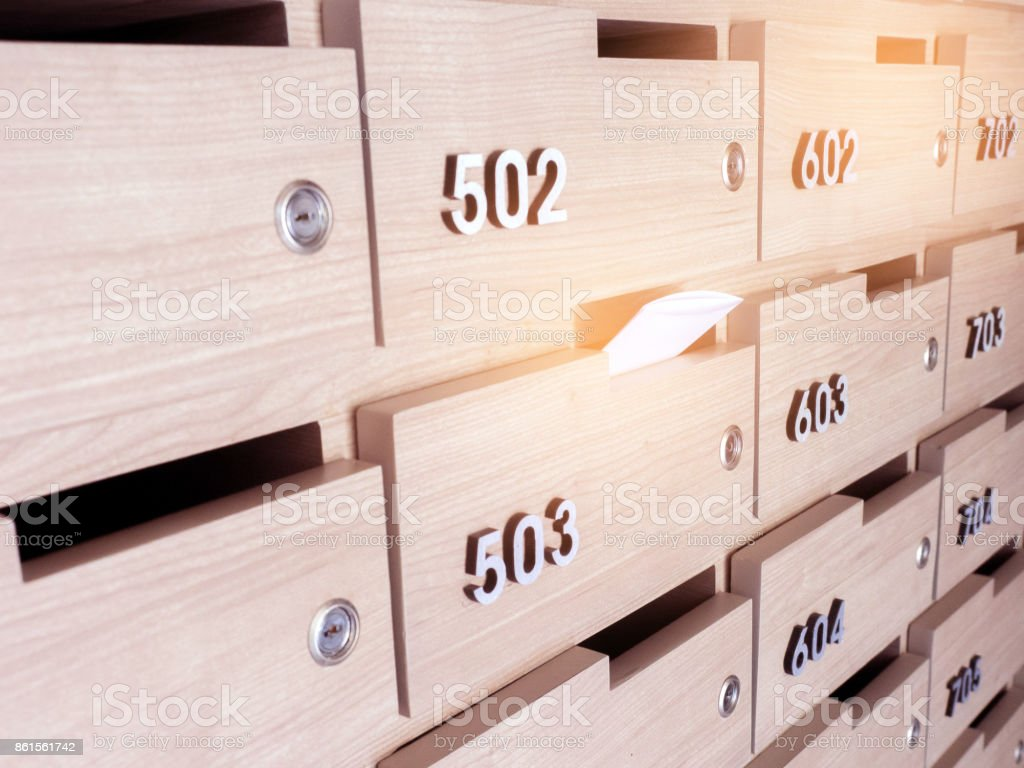 Close-up of person's hand . hand removing a letter from mailbox in the entrance hall of an apartment building stock photo