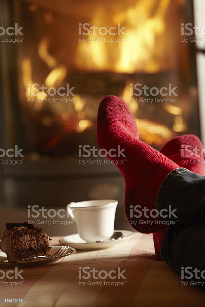 Close-up of person's red socks against cozy log fire stock photo