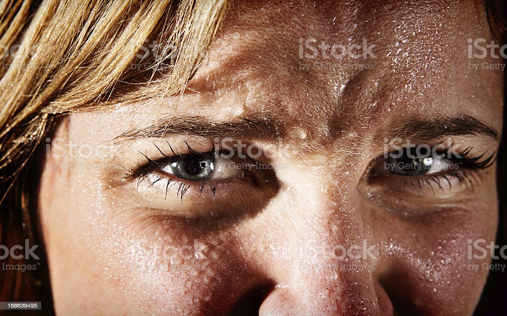 Close-up of perspiring, tense, frowning young blonde woman stock photo
