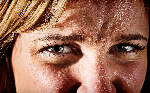 Close-up of perspiring, tensa, joven mujer rubia fruncir el ceño - foto de stock
