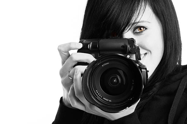 Close-up of photographer holding a camera in black and white stock photo