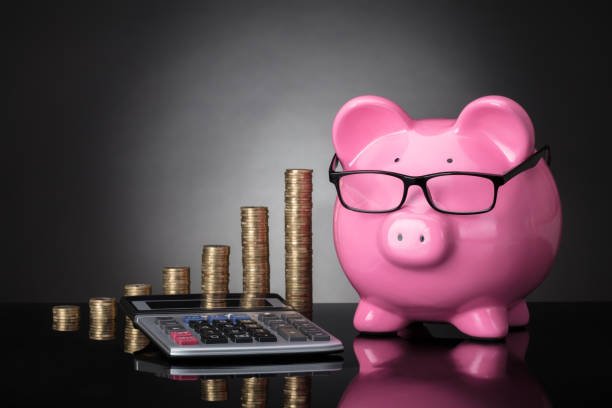 Close-up Of Piggy Bank, Calculator And Stacked Coins Close-up Of Pink Piggy Bank, Calculator And Stacked Coins On Grey Background 40 kilometre stock pictures, royalty-free photos & images