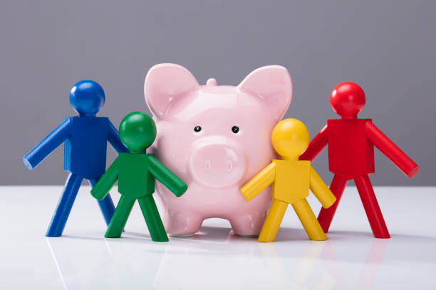 Close-up Of Piggybank And Human Figures Close-up Of Pink Piggybank And Multi Colored Human Figures Against Grey Background 40 kilometre stock pictures, royalty-free photos & images