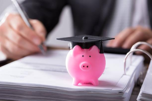 close-up of piggybank with graduation cap - кредит и кредитные карты стоковые фото и изображения