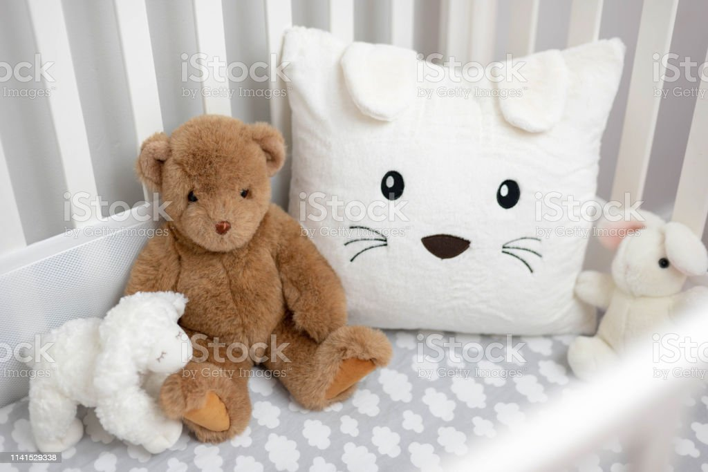 Cozy crib with stuffed animals in neutral soft gray and white palette