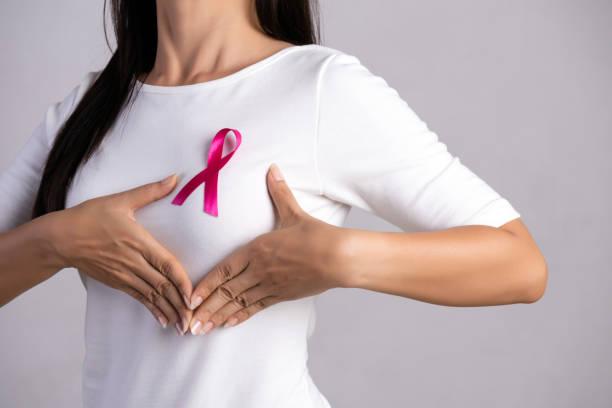 close up da fita cor de rosa do emblema na caixa da mulher para apoiar a causa do cancro da mama. saúde, medicina e conceito da consciência do cancro da mama. - outubro rosa - fotografias e filmes do acervo