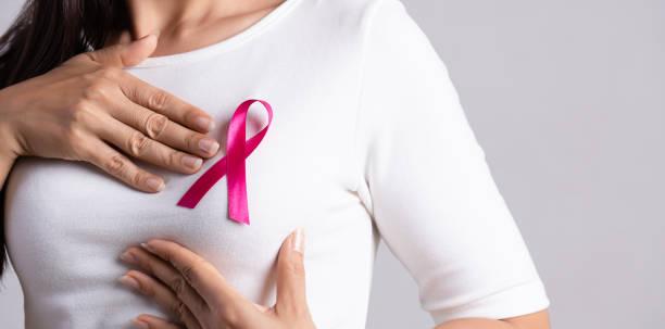 close-up de fita de distintivo rosa no peito da mulher para apoiar a causa do câncer de mama. conceito de conscientização sobre saúde, medicina e câncer de mama. - outubro rosa - fotografias e filmes do acervo