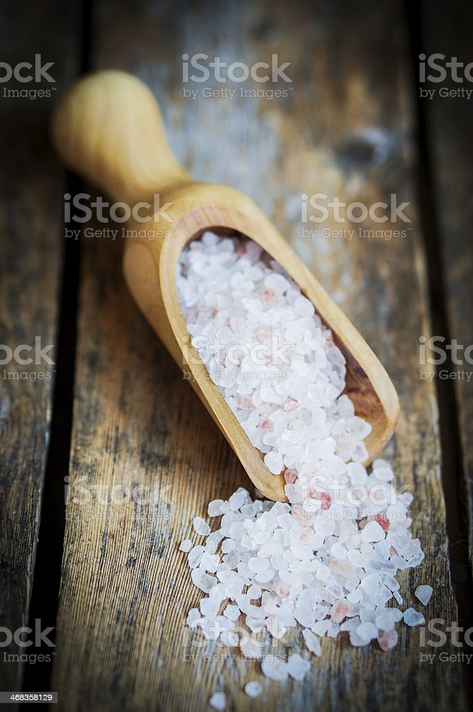 Closeup of pink hymalayan salt on rustic wooden background royalty-free stock photo