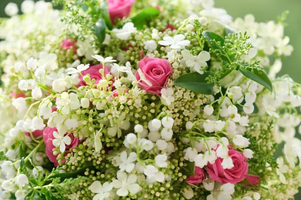 Primer plano de las rosas rosas flores y lirio blanco del valle con gotas - foto de stock