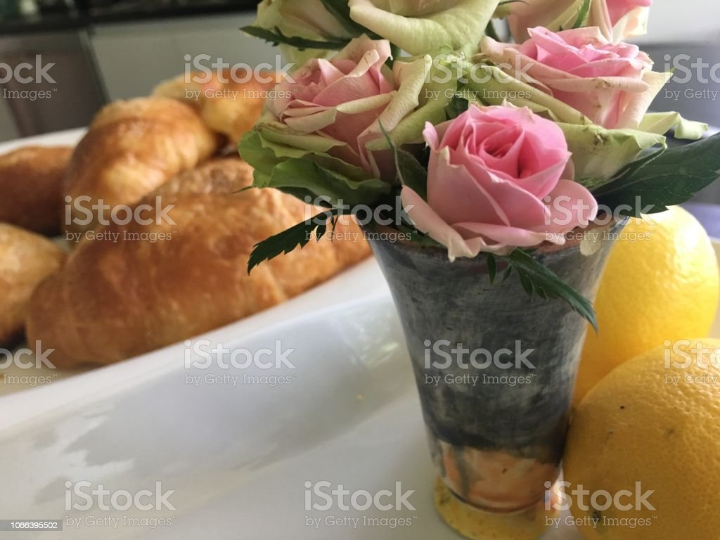 Closeup of Pink Roses next to croissants with lemon stock photo