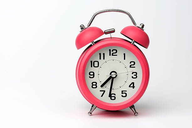 close-up of pink table alarm clock on white background - alarm clock stock photos and pictures