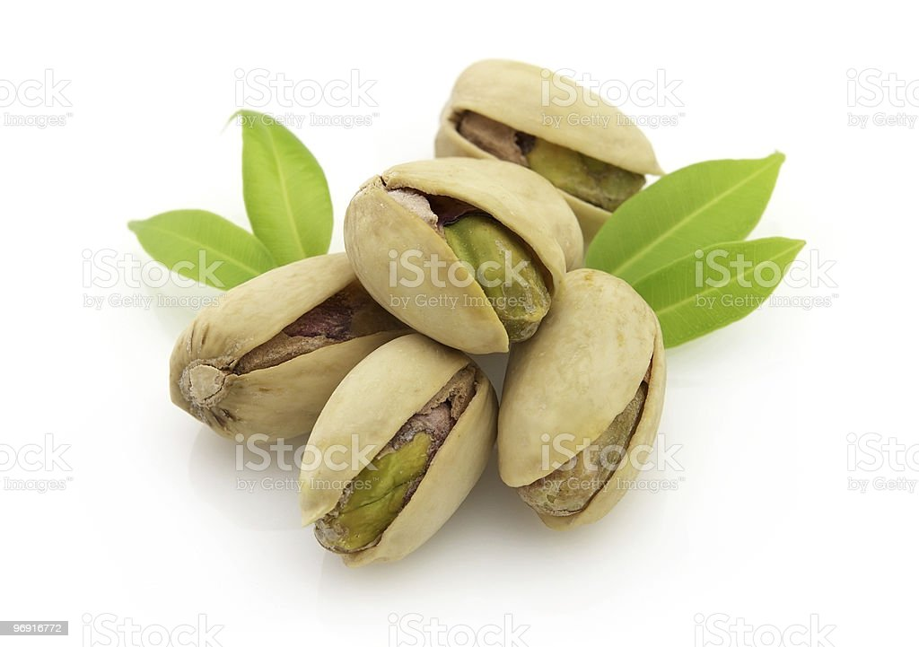 Close-up of pistachio nuts and leaves on white background royalty-free stock photo